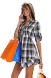 Young woman with shopping bags and cell phone Royalty Free Stock Photo