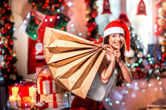 Young woman with shopping bags on Christmas. Young woman with shopping bags with Christmas decorations, candles, gifts and lights on bachground. Christmas sale stock photography