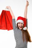 Young woman with shopping bags on Christmas. Happy young woman with red shopping bags on Christmas isolated on white background Royalty Free Stock Photo