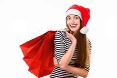 Young woman with shopping bags on Christmas. Happy young woman with red shopping bags on Christmas isolated on white background Stock Photos