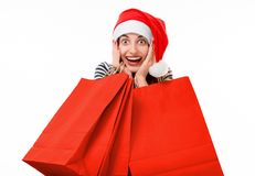 Young woman with shopping bags on Christmas. Happy young woman with red shopping bags on Christmas isolated on white background Stock Photo