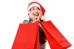 Young woman with shopping bags on Christmas. Happy young woman with red shopping bags on Christmas isolated on white background Royalty Free Stock Images