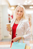 Young woman with shopping bags and coffee in mall Stock Photos