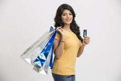 Young woman with shopping bags and credit card. Cheerful Indian young woman with shopping bags and credit card on white Stock Photos