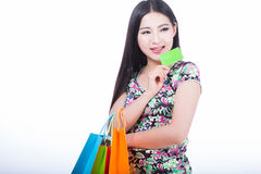 Young woman with shopping bags and credit card on a white backgr Royalty Free Stock Photography