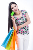 Young woman with shopping bags and credit card on a white backgr Stock Photo
