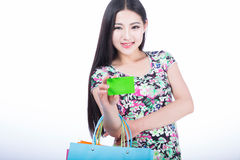 Young woman with shopping bags and credit card on a white backgr Stock Image