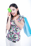 Young woman with shopping bags and credit card on a white backgr Royalty Free Stock Photos