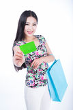 Young woman with shopping bags and credit card on a white backgr Stock Photos
