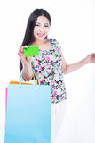 Young woman with shopping bags and credit card on a white backgr Stock Photography