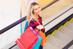 Young woman with shopping bags on escalator in the fashion store. Young blonde smiling attractive woman with long hair with a lot of color shopping bags on Stock Photo