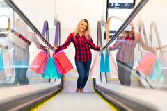 Young woman with shopping bags on escalator in the fashion store Royalty Free Stock Photography