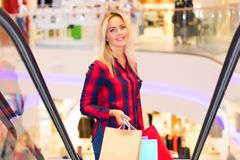 Young woman with shopping bags on escalator in the fashion store. Young blonde smiling attractive woman with long hair with a lot of color shopping bags on Royalty Free Stock Photo