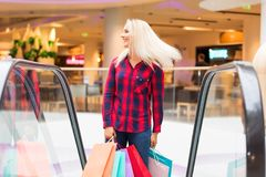 Young woman with shopping bags on escalator in the fashion store. Young blonde smiling attractive woman with long hair with a lot of color shopping bags on Royalty Free Stock Image