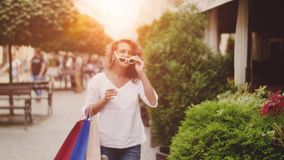 A young woman with shopping bags goes down the street and wears sunglasses. sunshine background.  stock footage