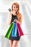 Young woman with shopping bags holding credit card Royalty Free Stock Photo