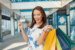 Young woman with shopping bags holding a credit card Stock Photos