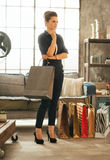 Young woman with shopping bags in loft apartment Stock Photos