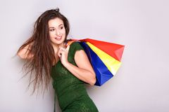 Young woman with shopping bags and looking behind. Portrait of young woman with shopping bags and looking behind Stock Images