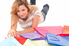 Young woman with shopping bags lying on floor Royalty Free Stock Photography