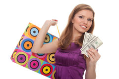 Young woman with shopping bags and money in hand Stock Photo