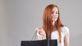 Young woman with shopping bags over white background. stock footage
