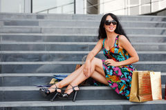 Happy woman sitting on the steps. Young woman with shopping bags sitting on the steps Stock Photos