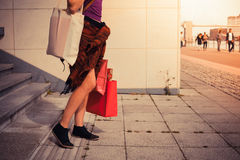 Young woman with shopping bags by stairs at sunset Stock Images