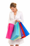 Young woman shopping bags standing look into isola. Young woman with shopping bags standing looking into bag isolated on white background royalty free stock photography