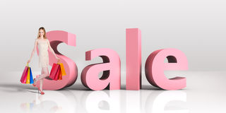 Young woman with shopping bags standing next to word SALE Stock Images