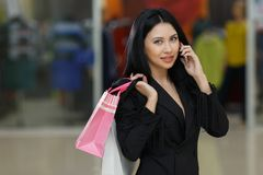 Young woman with shopping bags and talking on mobile phone in the mall. Happiness, consumerism, sale and people concept - young woman with shopping bags and Royalty Free Stock Photography