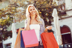 Young woman with shopping bags using mobile phone Royalty Free Stock Image