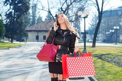 Young woman with shopping bags. Using telephone Royalty Free Stock Photo