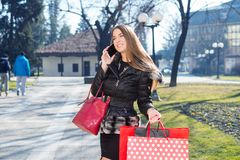 Young woman with shopping bags. Using telephone Stock Images