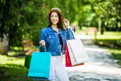 Young beauty woman with shopping bags walking in city park royalty free stock photo