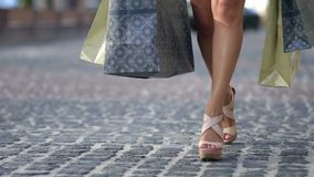 Young woman with shopping bags walking city street stock footage