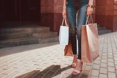 Young woman with shopping bags walking on city street in summer. Closeup of hands with purchases and heels. Sale royalty free stock image
