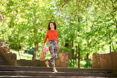 Young woman with shopping bags walking down the stairs outside Stock Photography