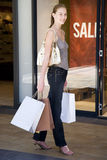 Young woman with shopping bags, walking down the street Stock Photo