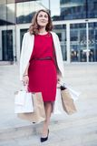 Young woman with shopping bags walking out from shop Stock Photo