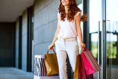 Young woman with shopping bags walking out from shop Royalty Free Stock Photography