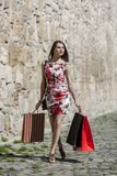 Woman with Shopping Bags in a City. Young woman with shopping bags walking on a small street in an old city Stock Photography