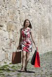 Woman with Shopping Bags in a City. Young woman with shopping bags walking on a small street in an old city Stock Image
