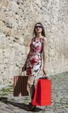 Woman with Shopping Bags in a City. Young woman with shopping bags walking in a small street of an old city Royalty Free Stock Photos