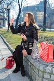 Young woman with shopping bags. Using telephone Stock Photography