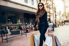 Young woman with shopping bags. Walking on street. Fashionable female model carrying shopping bags on road Royalty Free Stock Photo