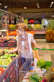 Young woman with shopping basket choosing apples. In grocery store Royalty Free Stock Photography