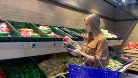 Young woman with shopping basket selecting fresh vegetables in a grocery store