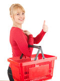 Young woman with shopping basket and thumb up Royalty Free Stock Photography