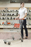 Young woman with shopping cart. Young woman with a shopping cart in a shoe store Royalty Free Stock Photography